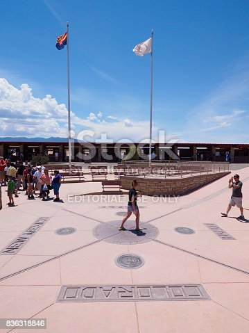 Four Corners Point, AZ - 24 July 2016: Tourists are taking pictures of the Four Corners Monument, touching point of the US states Utah, Arizona, Colorado and New Mexico.