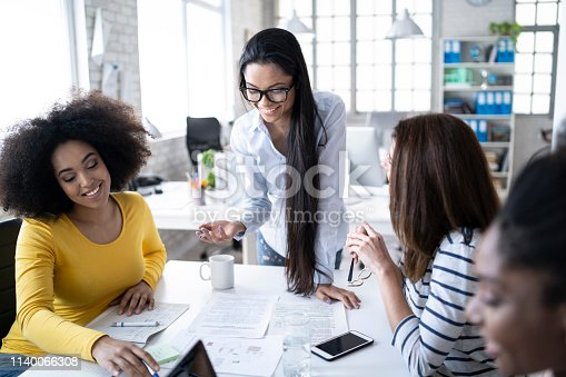 istock Four coworkers discussing ideas and using laptop at work 1140066308