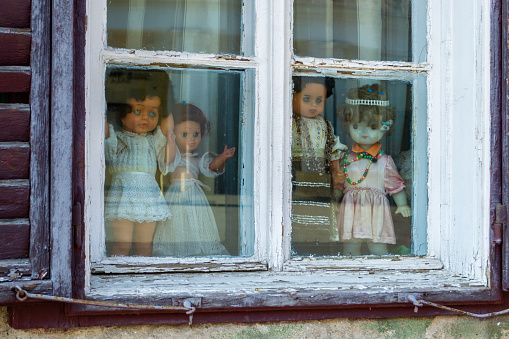 Four creepy dolls dressed in white and with traditional Romanian clothes, displayed in a window, while looking at the people passing by. Close up of puppets - horror concept.