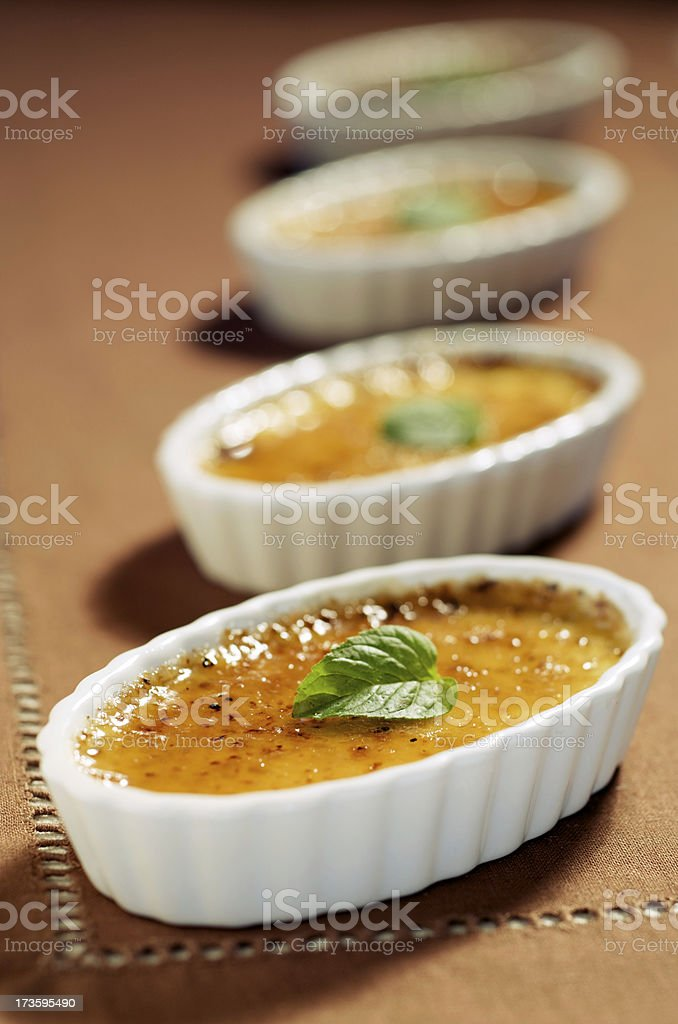 Four Creme Brulee (Burnt Cream) Desserts in White Ramekins stock photo