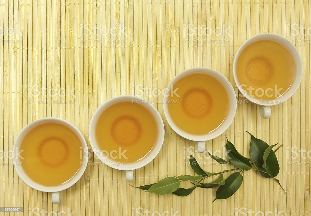 four cups of tea and green leaves on the mat royalty-free stock photo