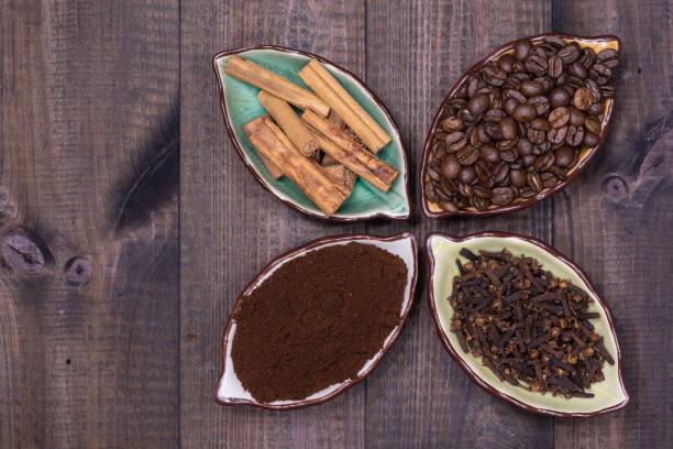 Vier Tassen mit Kaffeebohnen, Zimt, Nelken und Kaffeepulver – Foto