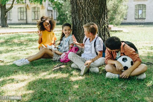 four cute multicultural schoolkids talking while sitting on lawn under tree