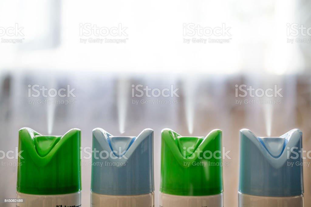 Quatre cylindres de désodorisant dans une rangée. - Photo