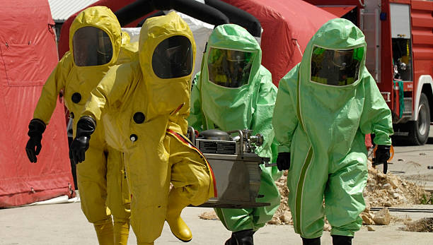 Four decontamination operatives at work in green and yellow chemical workers decontamination stock pictures, royalty-free photos & images