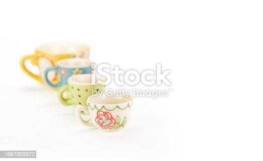 Four teacups in a row on white background. Shallow depth of field with focus on closest cup. Varying colours, patterns and sizes in ascending order. Pretty bright pastel colours. With copy space.