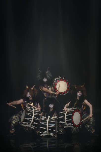 four demons from japanese mythology. full lenght portrait of artists drummers taiko in a wig with horns and make-up on stage against a dark background. - theatre full of people stage foto e immagini stock