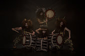 日本神話の4人の悪魔暗い背景に対して、ホーンとメイクアップでかつらで太鼓を太鼓を太鼓のフルレングスの肖像画。