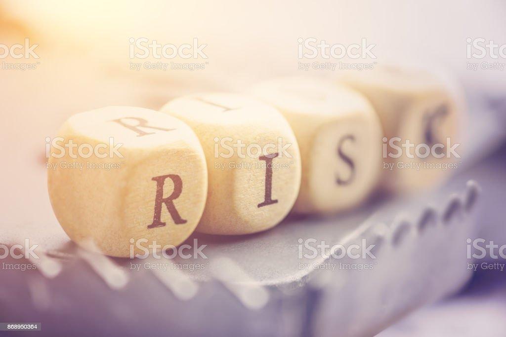 Cuatro dados se arreglan en una palabra «Riesgo» en una trampa de la rata. Riesgo implica la posibilidad de retorno real de la inversión será diferente de retorno esperado, incluye la posibilidad de pérdida de la inversión original. - foto de stock