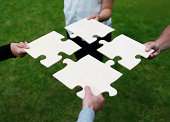 istock Four different people connecting large puzzle pieces 471441475
