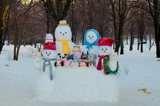 Four different size dressedsnowmen and animals made of snow near trees outdoors in winter