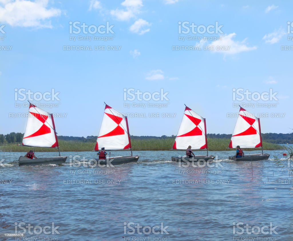 Four Dinghy With A Redwhite Sails Sailboats Go In A Dense
