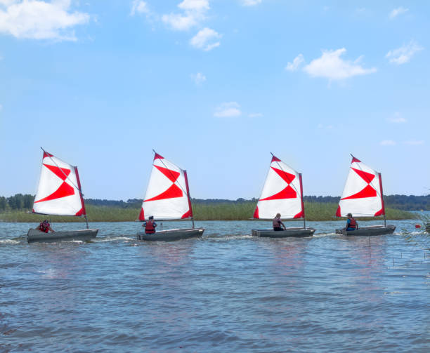 Four dinghy with a red-white sails. Sailboats go in a dense state PARENTIS-EN-BORN, FRANCE - JULY 25, 2018: Four dinghy with a red-white sails on the lake. Sailboats go in a dense state. Sunny summer day sailing dinghy stock pictures, royalty-free photos & images