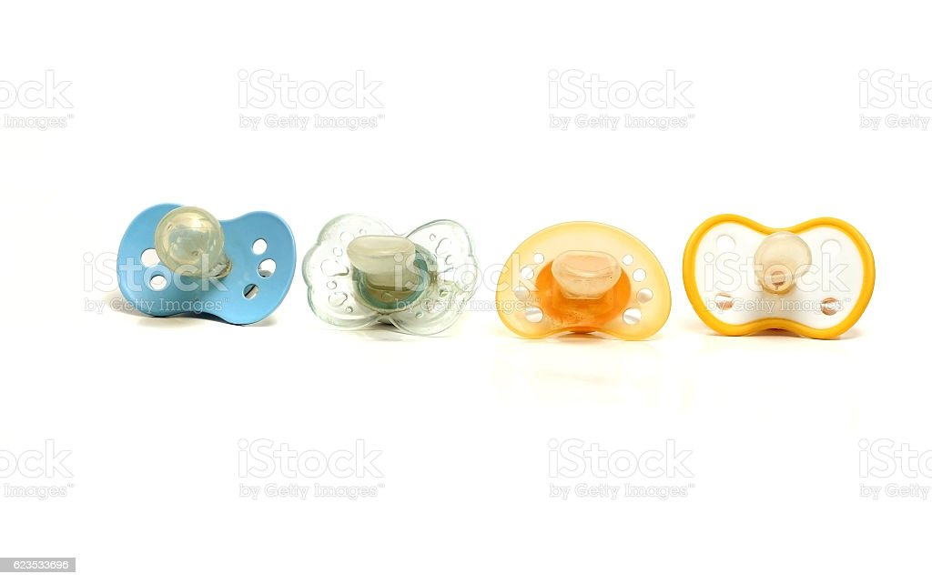 four dirty pacifiers on a white background stock photo