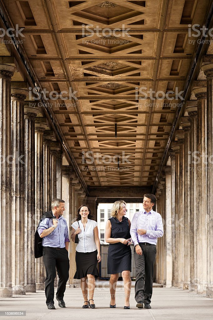 Four Elegant People Walking in Columns Passage royalty-free stock photo