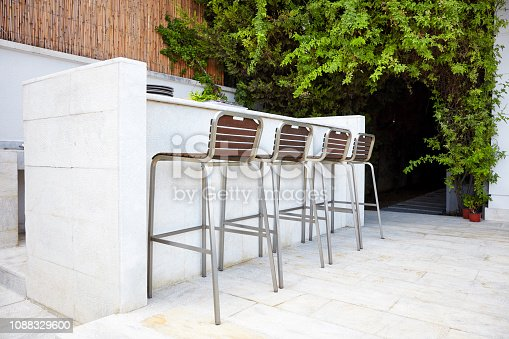Four empty bar stool chairs with wooden seats and metal foot near a white concrete bar counter in an outdoor bar