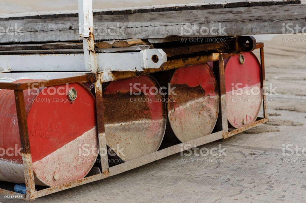 Four empty rusty red barrels. Details of the old wooden pontoon bridge. The sign from the water zbiór zdjęć royalty-free