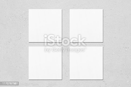 Four empty white square business card mockups with soft shadows on neutral light grey concrete background. Flat lay, top view