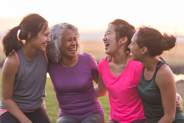 four ethnic women laughing together after an outdoor workout - só mulheres imagens e fotografias de stock