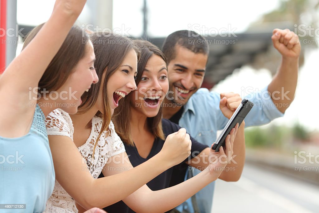 Four euphoric friends watching a tablet stock photo