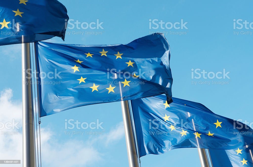 Four European Union flags waving in the wind stock photo