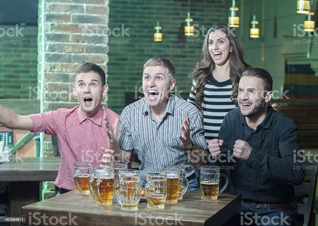 Four excited friends at a pub yelling while drinking beer royalty-free stock photo