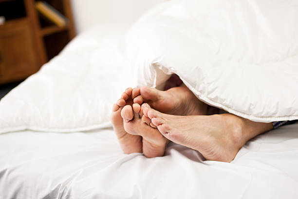 four feet sticking out from underneath blankets - old man feet stock photos and pictures