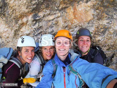 istock four female climbers celebrate on the mountain summit by taking 1186902546
