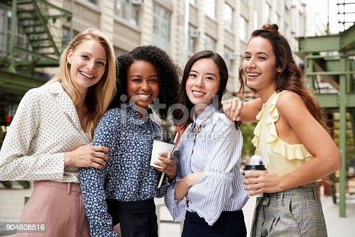 istock Four female coworkers smiling to camera outside 904608516