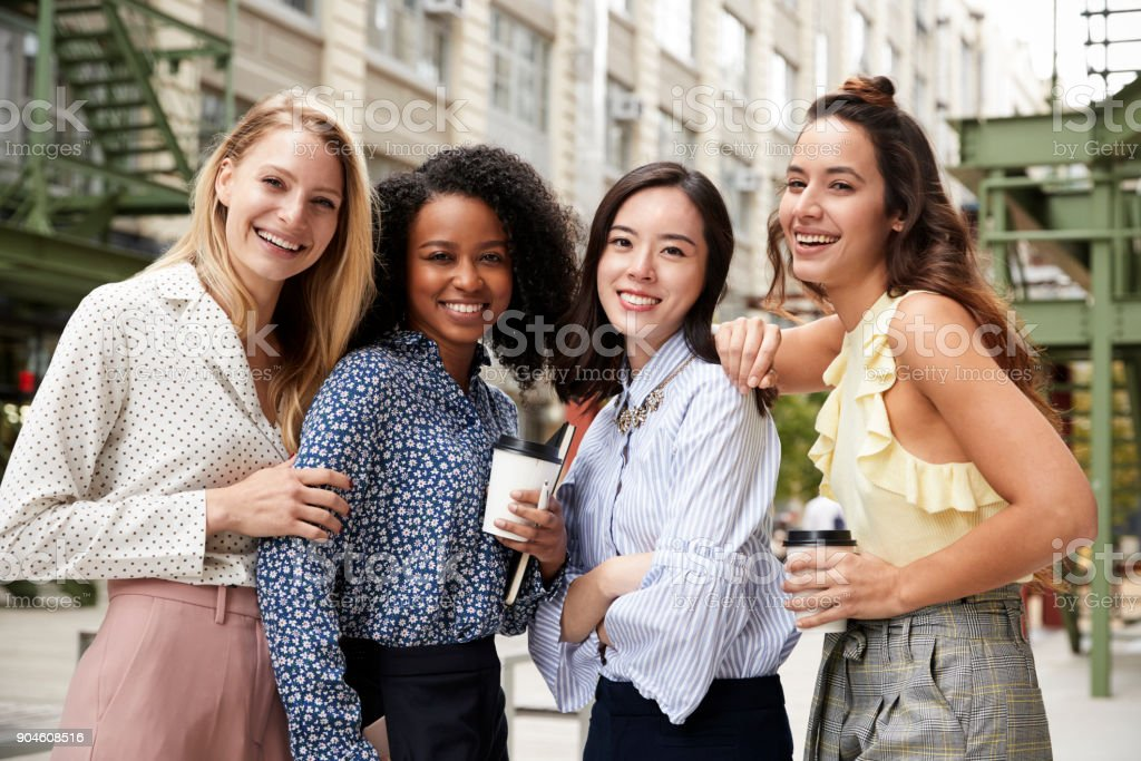 Four female coworkers smiling to camera outside stock photo