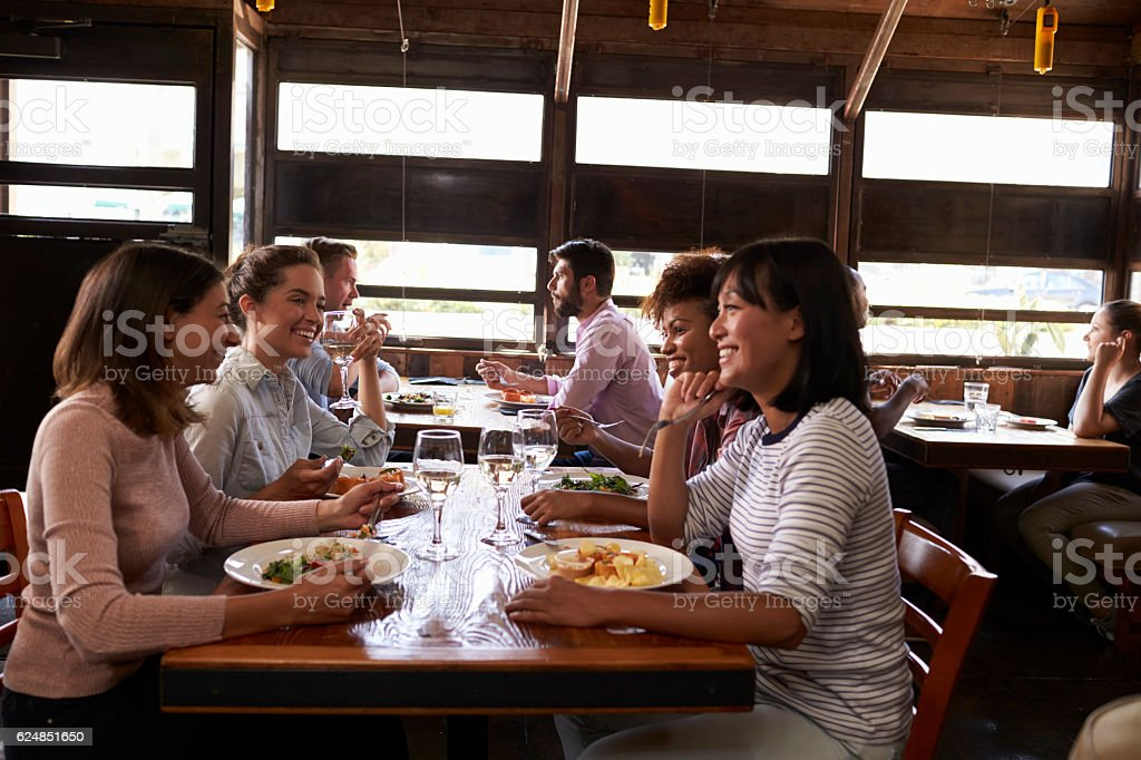 Four female friends at a girls' lunch in a busy restaurant stock photo