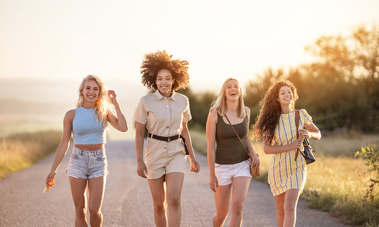 Four female friends having a walk on a country road and having fun
