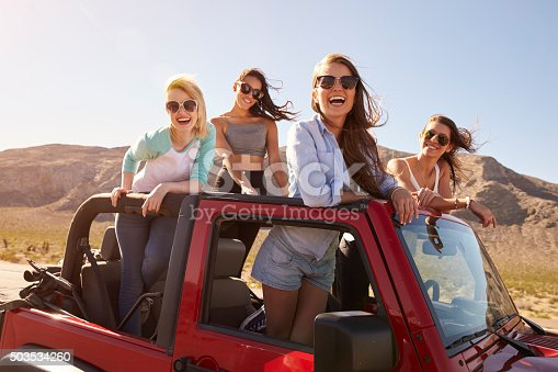 503545320istockphoto Four Female Friends On Road Trip Standing In Convertible Car 503534260