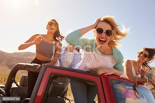 503545320 istock photo Four Female Friends On Road Trip Standing In Convertible Car 503534744