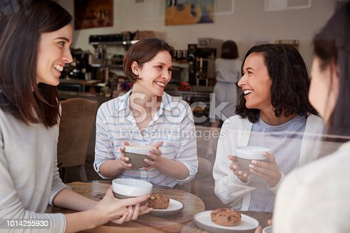 Four female friends relaxing over coffee at a coffee shop