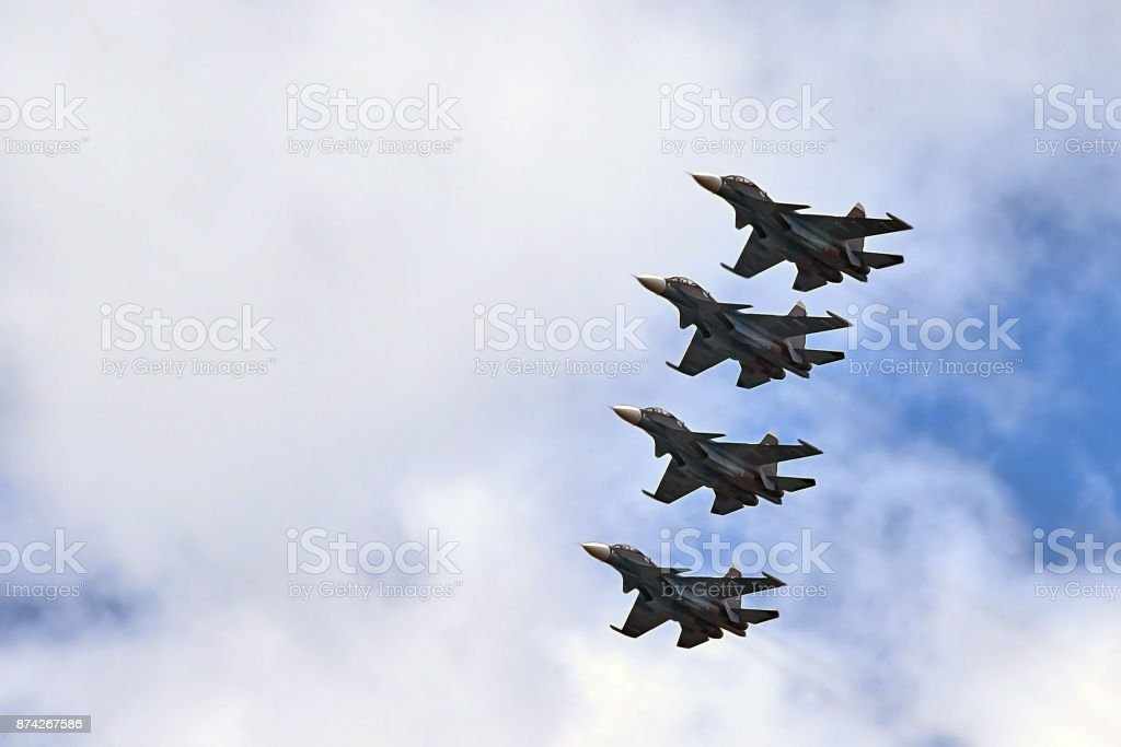 four fighters jet flying in formation against a blue sky stock photo