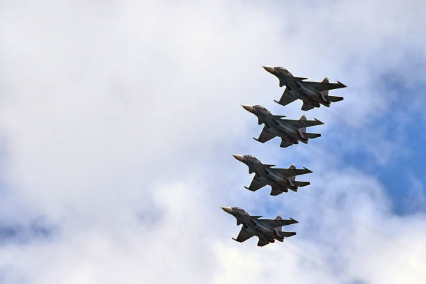 four fighters jet flying in formation against a blue sky - airshow stock photos and pictures