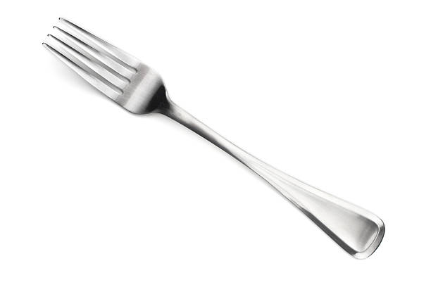 A four fingered stainless steel fork made in Sheffield Close up isolated shot of a fork. fork stock pictures, royalty-free photos & images