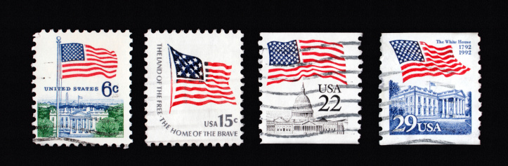 Four canceled first class stamps with United States of America flags of different value on black backgroundMore images with stamps: