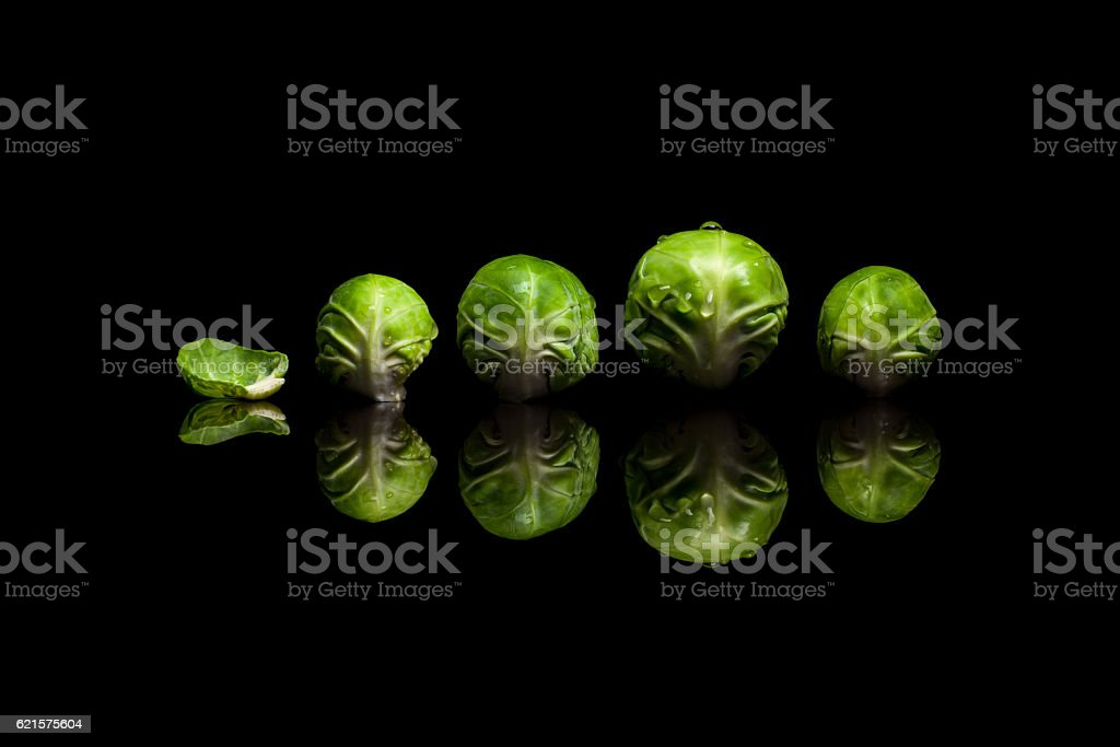 Four fresh green brussels sprouts in row isolated on black photo libre de droits