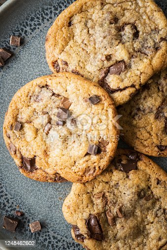 Four freshly baked chocolate chip cookies on a blue ceramic plate. Loose chocolate chips are scattered around the plate.