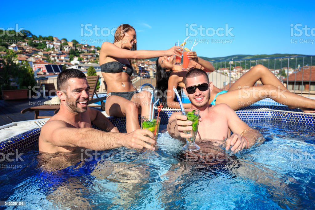 Quatre amis, boire des cocktails sur la piscine sur le toit - Photo