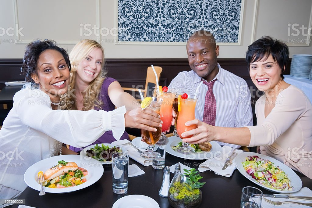 Four friends eating and giving cheers with cocktails royalty-free stock photo
