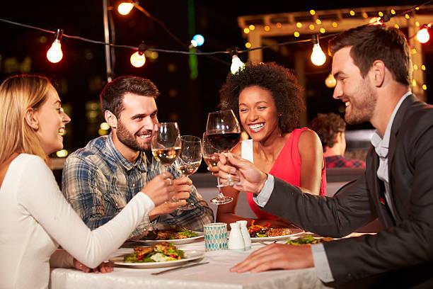 four friends eating dinner at rooftop restaurant - akşam yemeği yemek stok fotoğraflar ve resimler