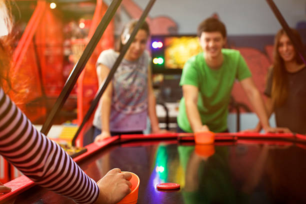 Four friends having fun and playing air hockey game stock photo