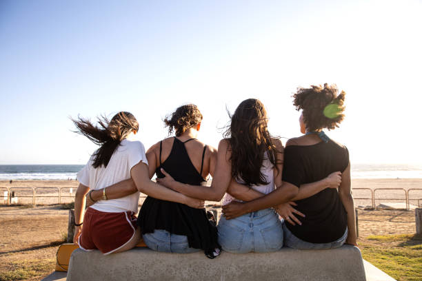 Four friends hugging sitting on bench in front of a beach stock photo