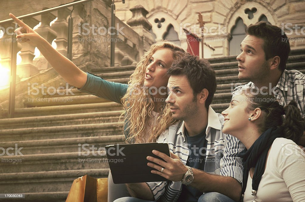 Four friends looking something with a tablet in their hands stock photo