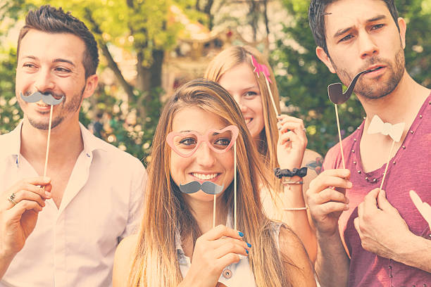 Four friends making faces in a photo booth pose stock photo