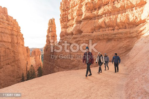 A quartet of friends in their 20s head out on a day hike through the stunning cliffs and landscapes of Utah's Bryce Canyon National Park. They are surrounded by towering, jagged pinnacles of rocks and ridges.