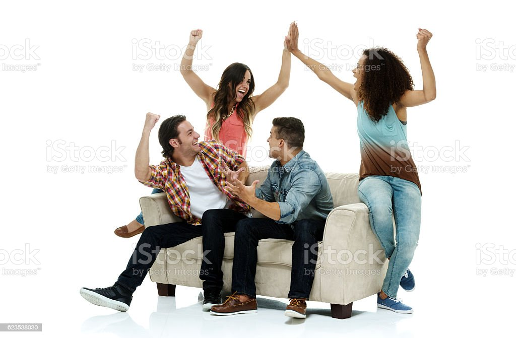 Four friends on couch and cheering stock photo